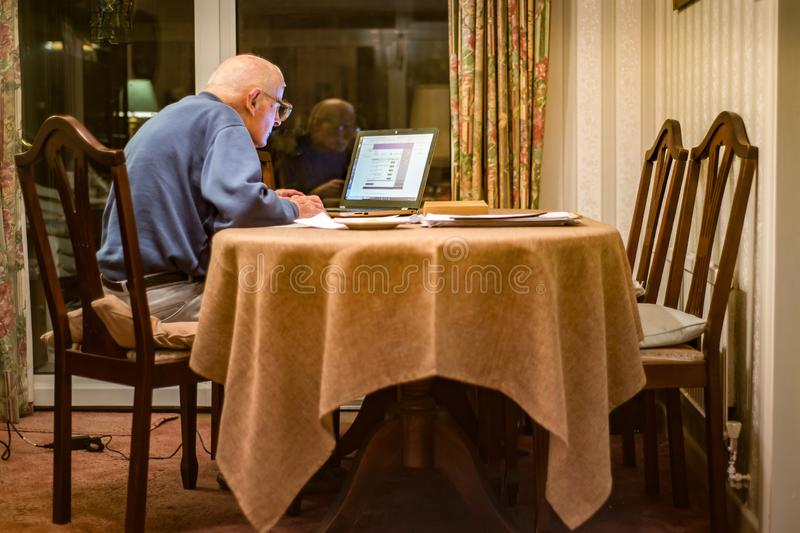 Homme plus âgé utilisant un ordinateur portable pour vérifier ses portefeuilles d'actions, Hampshire, Angleterre, U k photos stock