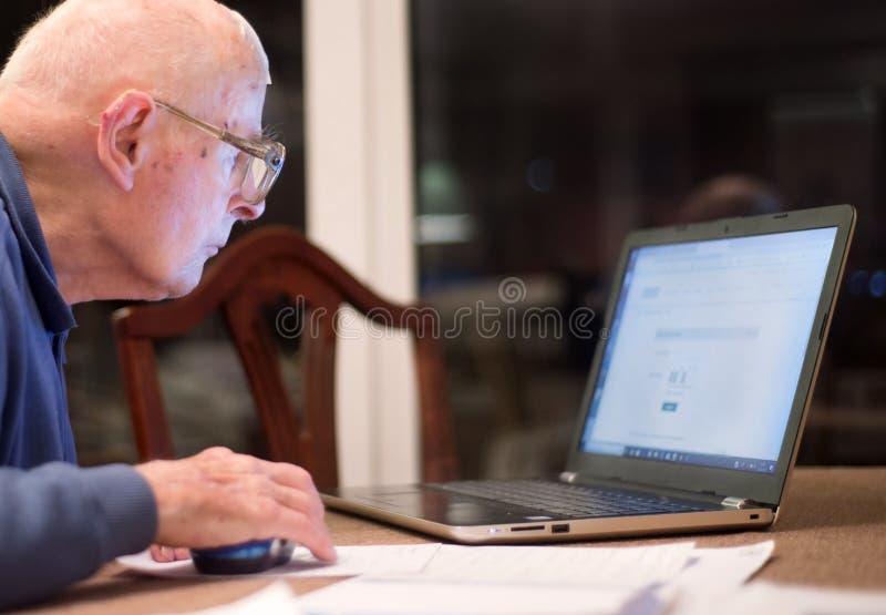 Homme plus âgé utilisant un ordinateur portable, vérifiant ses portefeuilles d'actions, le Hampshire, Angleterre, U k images libres de droits