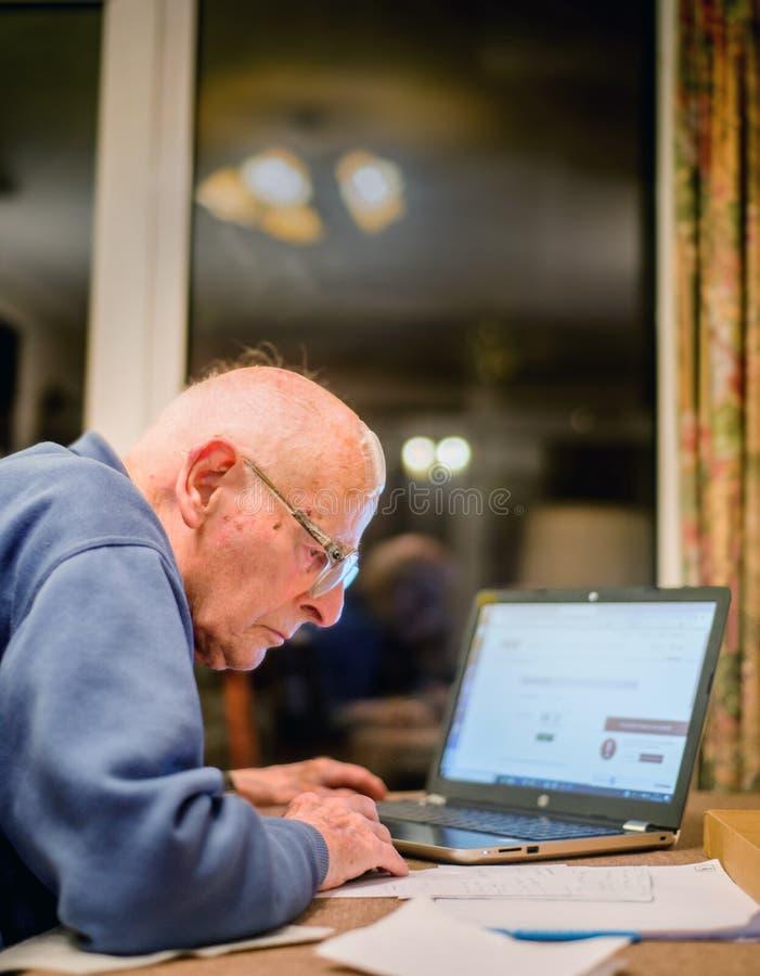 Homme plus âgé utilisant un ordinateur pour vérifier ses portefeuilles d'actions, Hampshire, Angleterre, U k photo libre de droits
