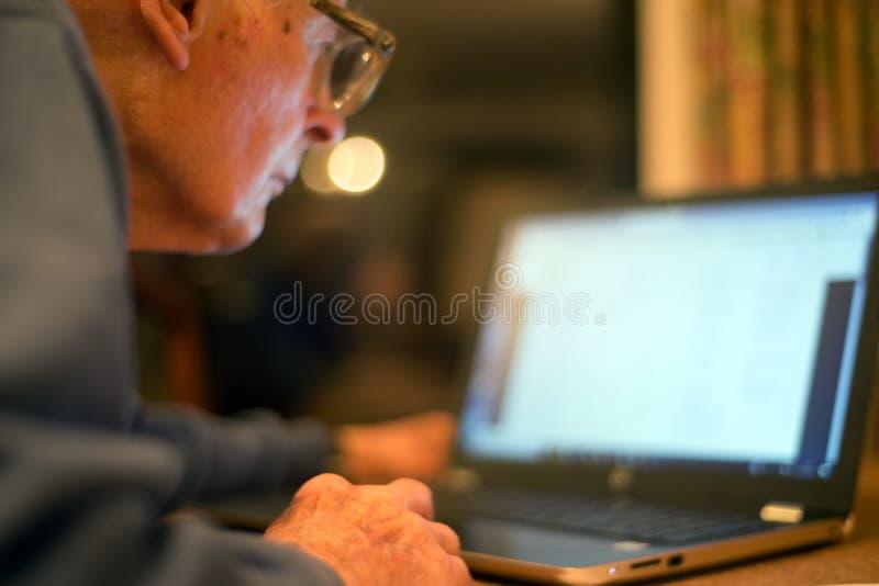Homme plus ?g? se renseignant sur l'Internet, utilisant un ordinateur portable pour v?rifier ses portefeuilles d'actions, le Hamp photographie stock