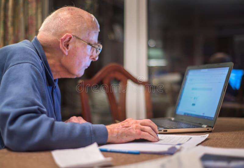 Homme plus ?g? utilisant un ordinateur portable pour v?rifier des portefeuilles d'actions, Hampshire, Angleterre, U k image stock