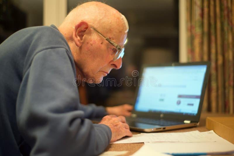 Homme plus ?g? utilisant un ordinateur portable pour v?rifier des portefeuilles d'actions, Hampshire, Angleterre, U k image libre de droits