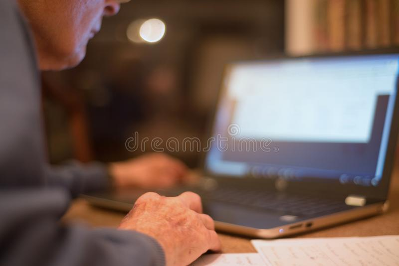 Homme plus ?g? utilisant un ordinateur portable pour v?rifier ses portefeuilles d'actions, Hampshire, Angleterre, U k photo libre de droits