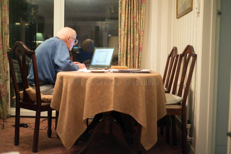 Homme plus ?g? utilisant un ordinateur portable pour v?rifier ses portefeuilles d'actions, Hampshire, Angleterre, U k photos libres de droits