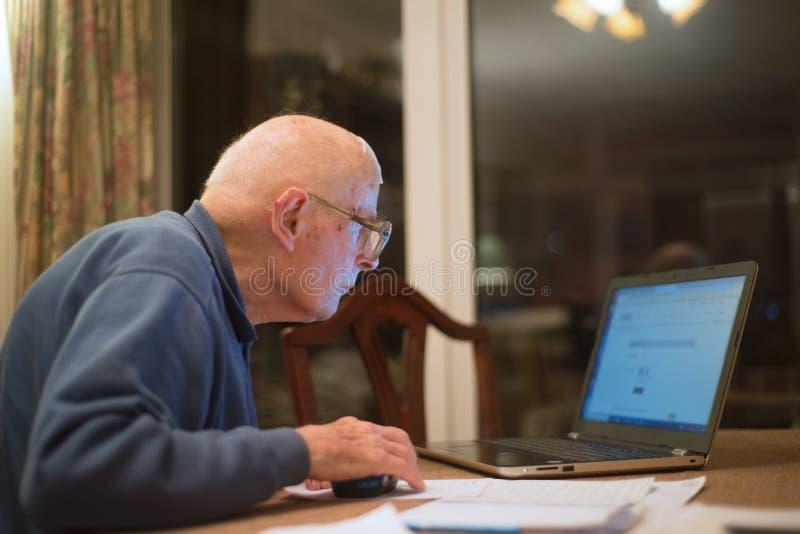 Homme plus ?g? utilisant un ordinateur portable, v?rifiant ses portefeuilles d'actions, le Hampshire, Angleterre, U k image libre de droits
