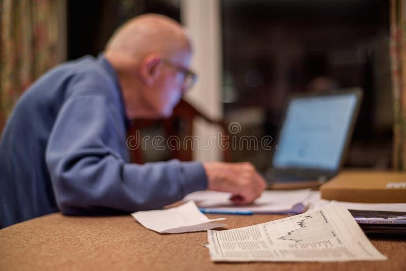 Homme plus ?g? utilisant un ordinateur pour v?rifier ses portefeuilles d'actions, Hampshire, Angleterre, U k image libre de droits
