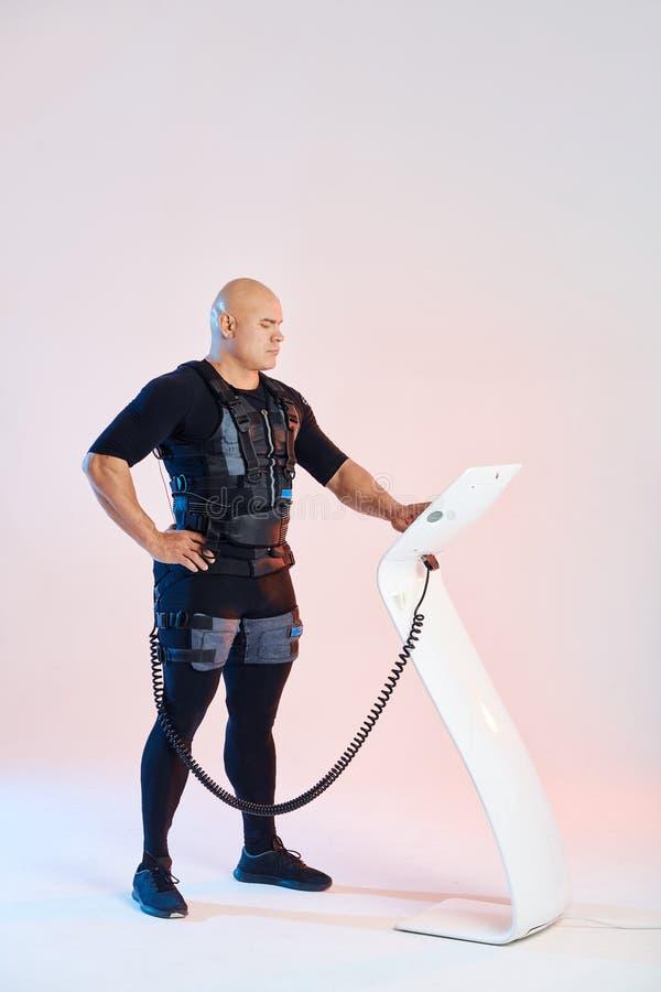 Homme portant la position musculaire ?lectrique de costume de stimulation pr?s du comprim? de SME images libres de droits