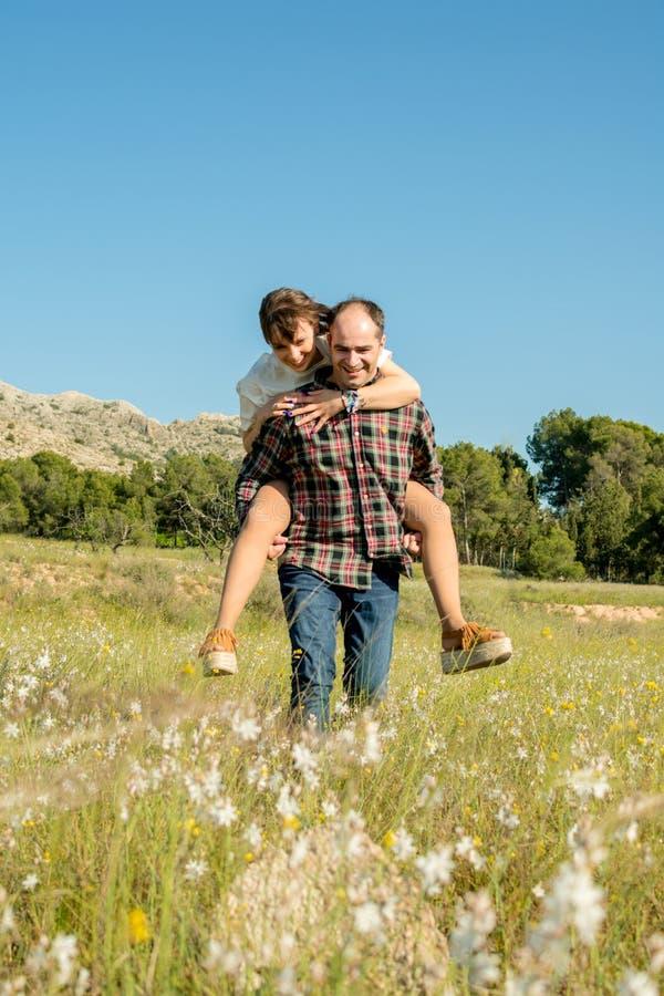 Homme portant son ?pouse sur le dos sur le sien de retour photographie stock libre de droits