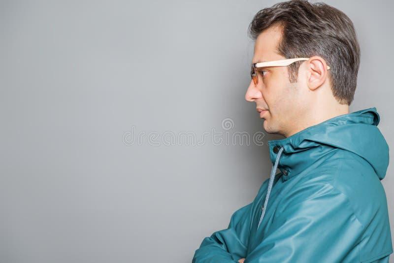 Homme portant un portrait vert de studio d'imperm?able photographie stock libre de droits