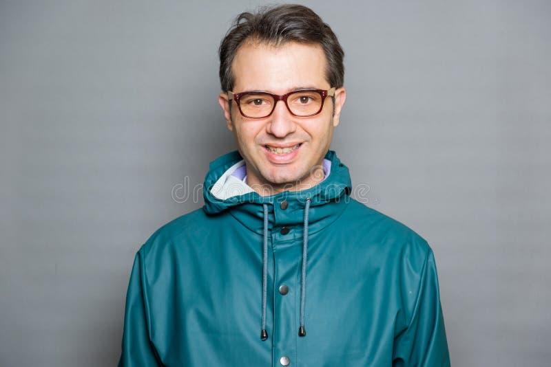 Homme portant un portrait vert de studio d'imperm?able photos libres de droits