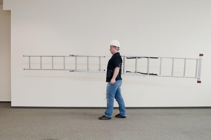 Homme portant une échelle images stock