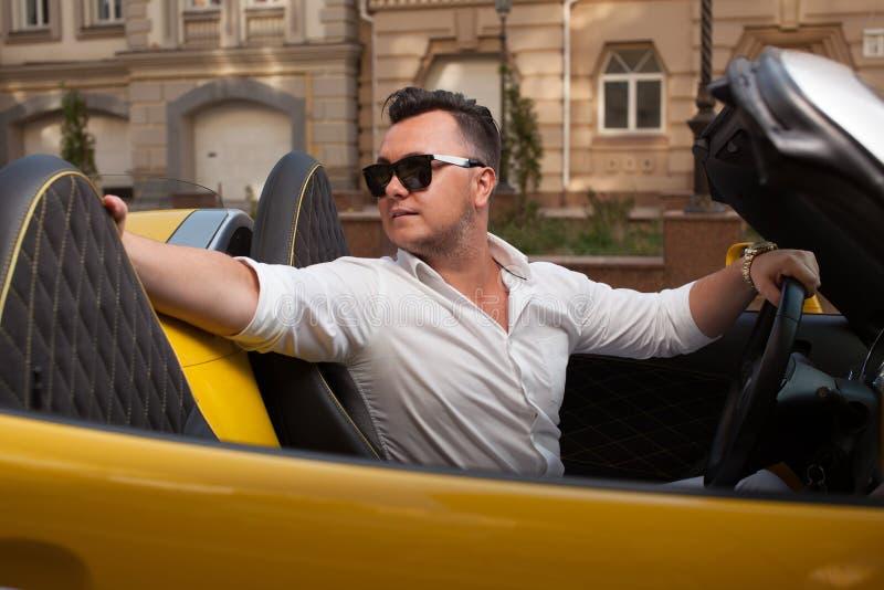 Homme posant avec sportcar convertible photographie stock