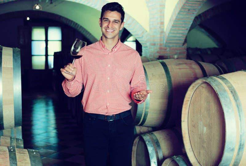 Homme posant dans la cave d'établissement vinicole photo stock