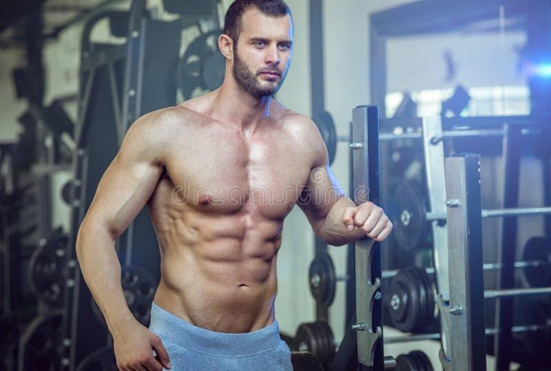 Homme posant dans le gymnase montrant l'ABS photos stock