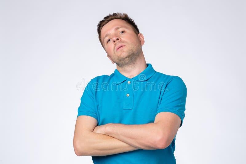 Homme posant dans le studio avec des bras croisés et regardant fixement la caméra avec le regard vaniteux arrogant photo stock