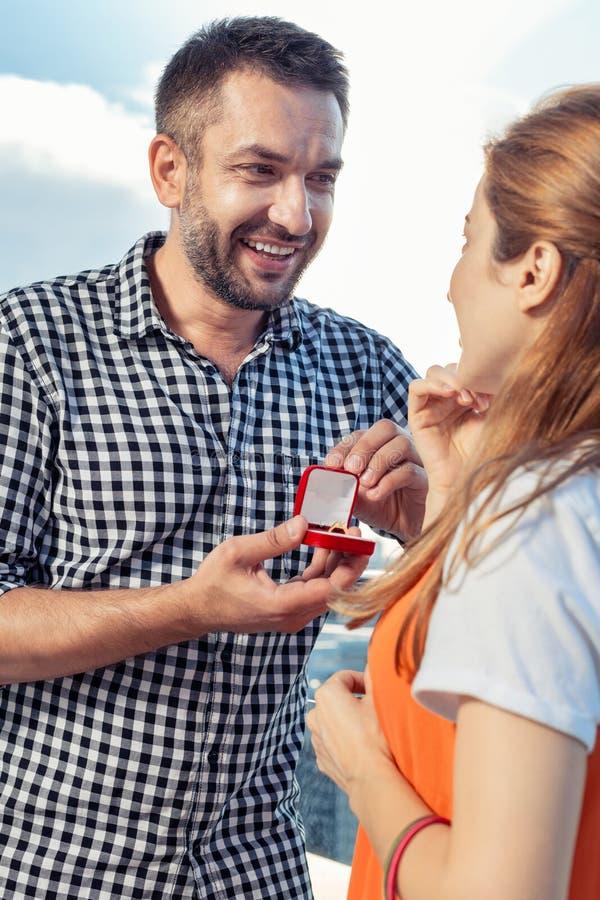 Homme positif joyeux faisant une proposition à son amie images stock