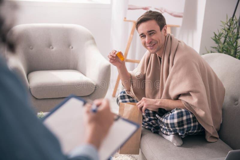 Homme positif joyeux tenant sa médecine images stock