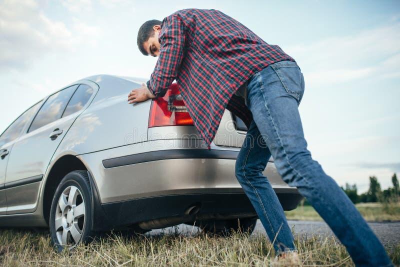 Homme poussant la voiture cassée, vue de côté image stock