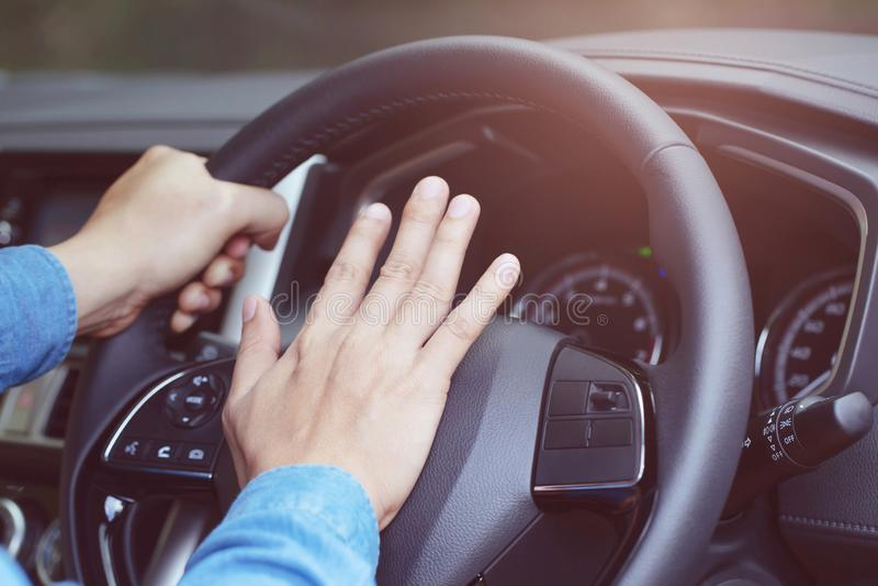 Homme poussant le klaxon tout en conduisant la séance d'une voiture de presse de volant, images stock