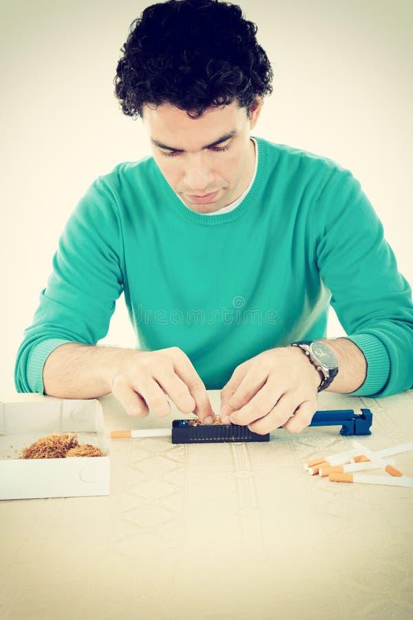 Homme préparant des cigares et roulant le tabac image libre de droits