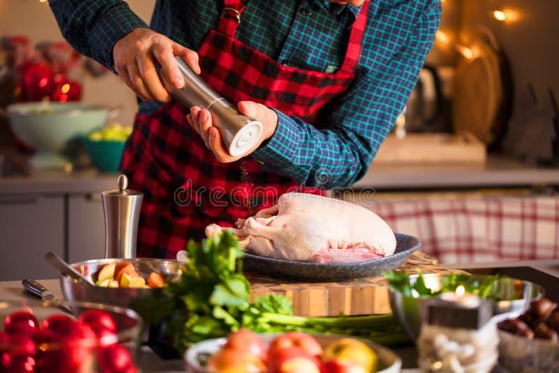 Homme préparant la nourriture délicieuse et saine dans la cuisine à la maison pour le canard ou l'oie de Noël de Noël image stock