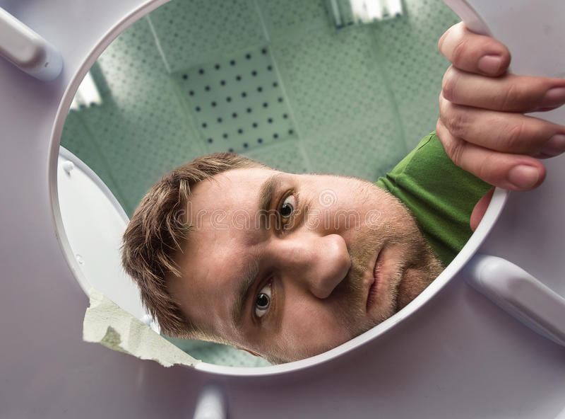 Homme prêt à vomir dans la cuvette des toilettes photos stock