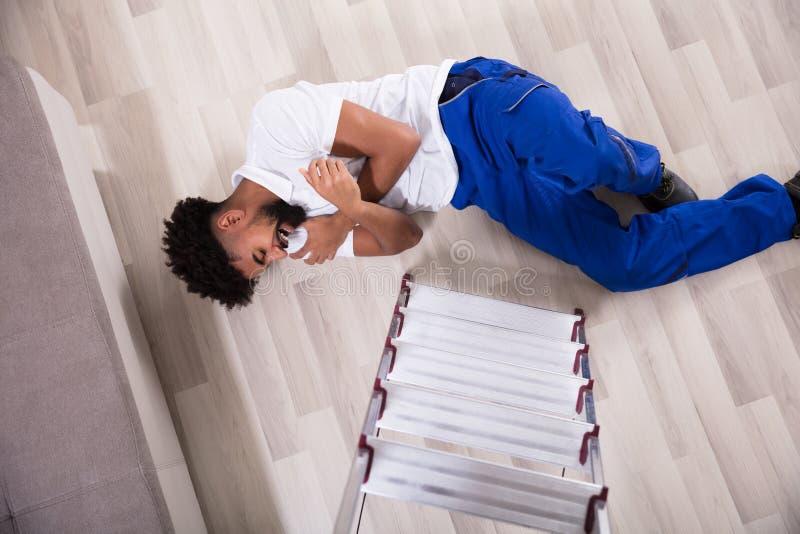 Homme pratique tombant de l'échelle dans le salon photo libre de droits
