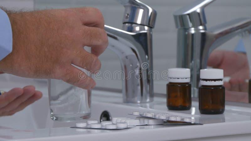 Homme prenant des pilules avec de l'eau dans la salle de bains pour le mal de tête image stock