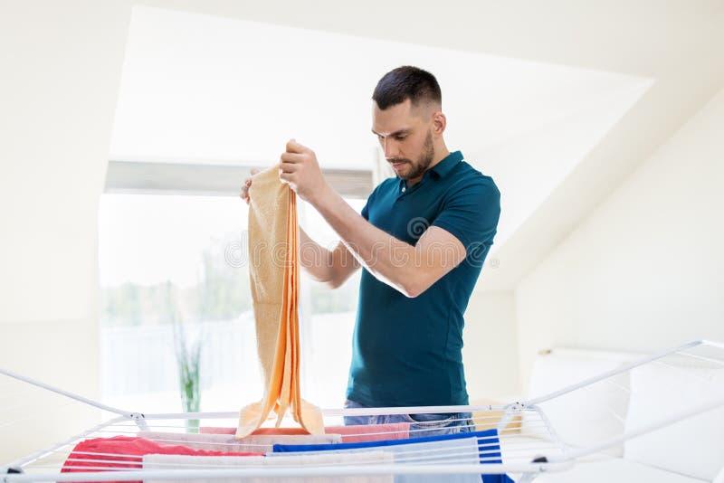 Homme prenant la blanchisserie du support de séchage à la maison photographie stock libre de droits