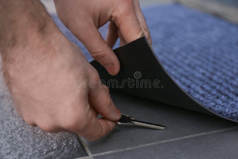 Homme prenant la clé cachée sous le tapis de porte images stock