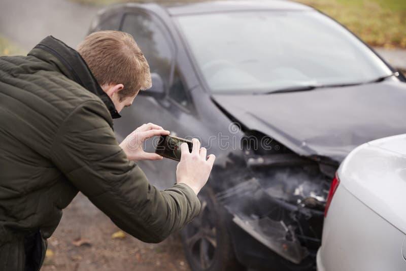 Homme prenant la photo de l'accident de voiture au téléphone portable photographie stock libre de droits