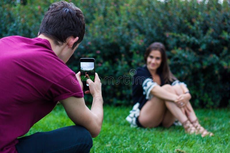 Homme prenant la photo des femmes avec le téléphone intelligent image libre de droits