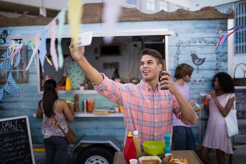Homme prenant le selfie avec la bouteille à bière du mobile image stock