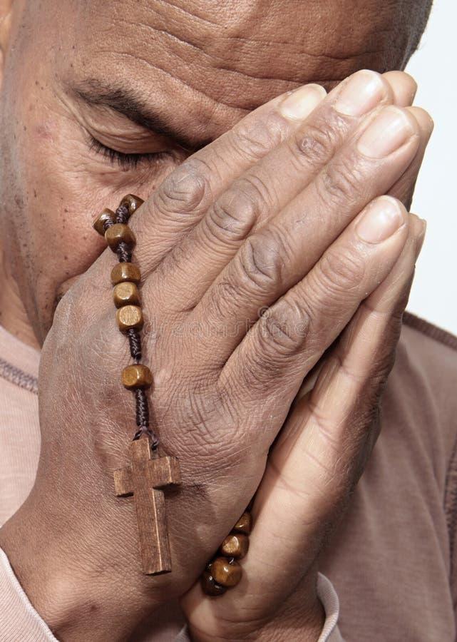 Homme priant à un dieu avec des perles de chapelet dans des ses mains photographie stock