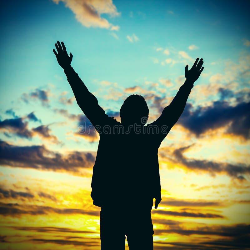 Homme priant sur le fond de coucher du soleil image libre de droits