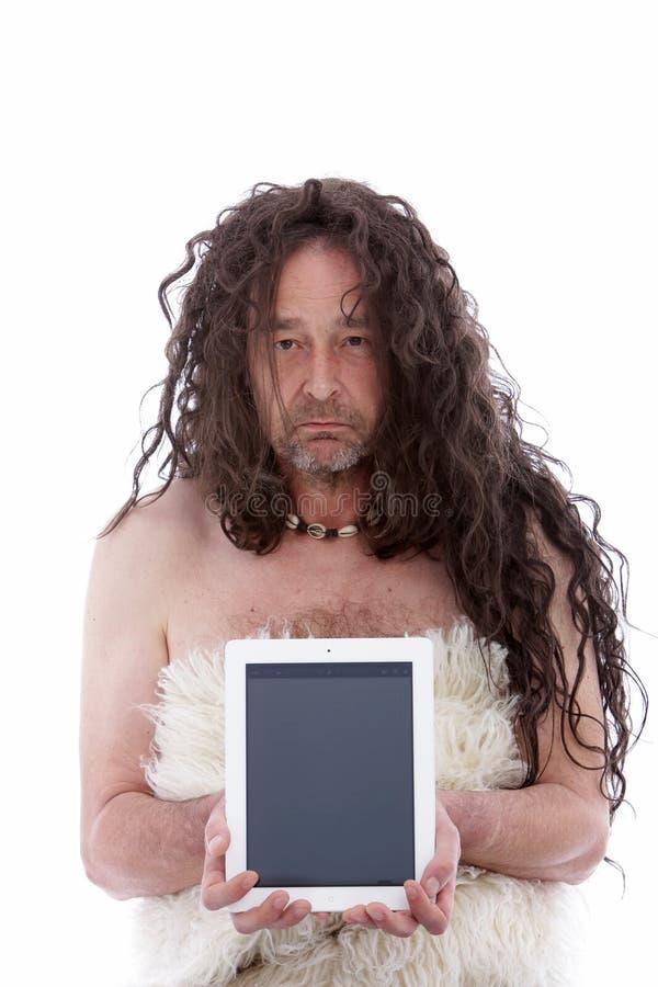 Homme primitif drôle tenant un comprimé de PC photos libres de droits