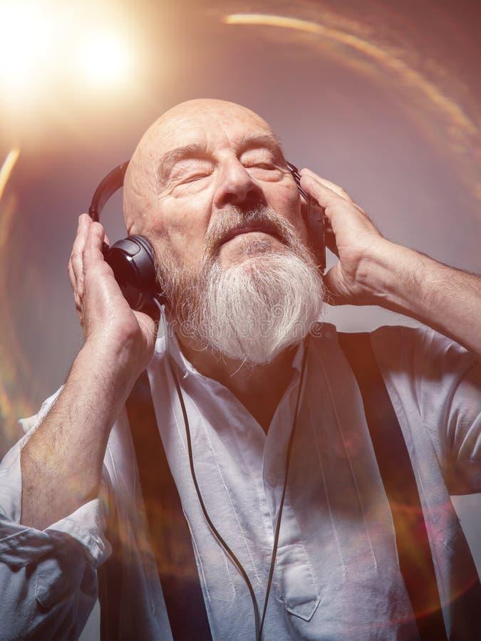 Homme principal chauve plus âgé avec des écouteurs image libre de droits