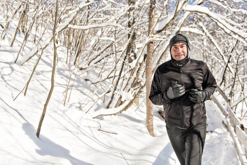 Homme pulsant sur la neige dans la forêt, jour d'hiver ensoleillé bautiful image libre de droits