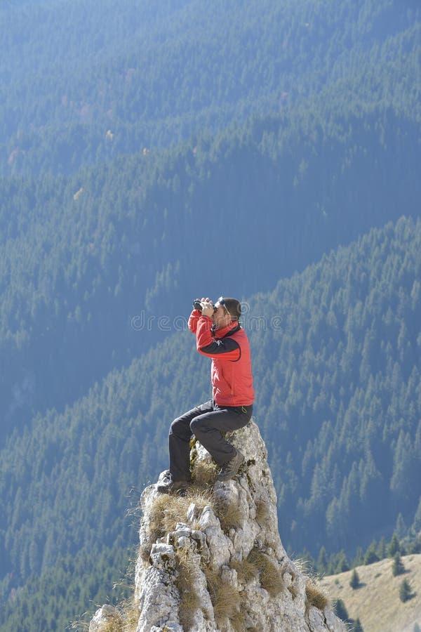Homme qui étudie l'itinéraire de touristes dans les montagnes images stock