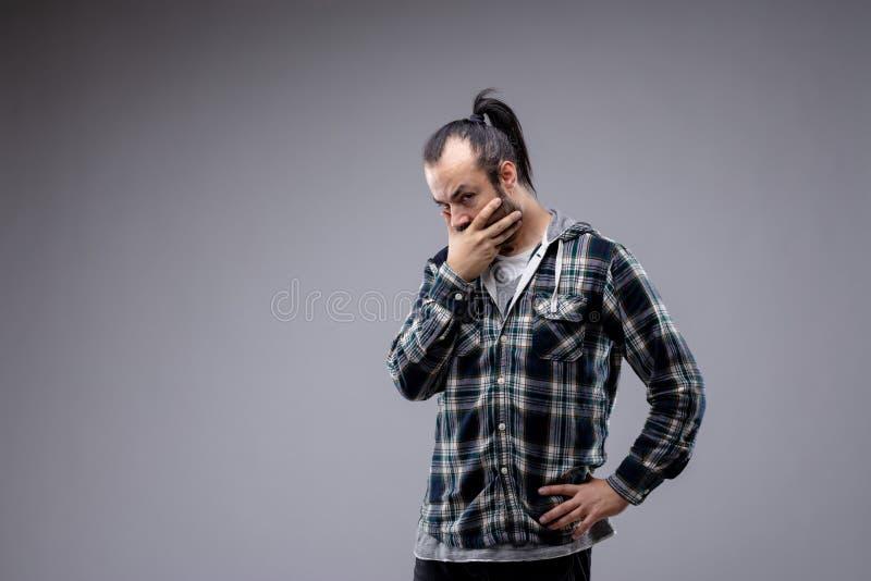 Homme réfléchi observant la caméra avec le scepticisme photographie stock libre de droits