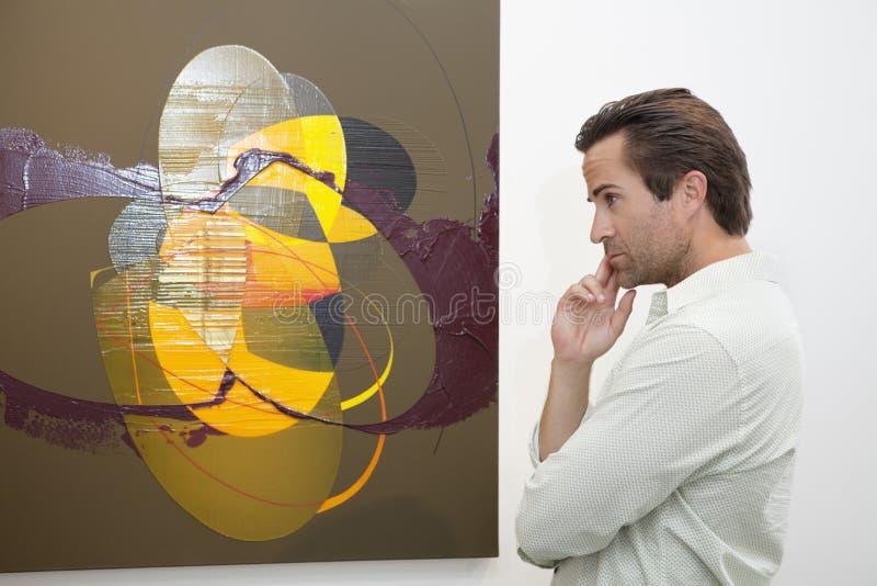 Homme réfléchi regardant la peinture de mur dans la galerie d'art images libres de droits