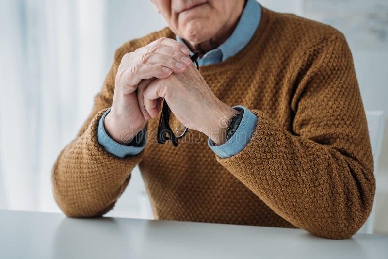 Homme réfléchi supérieur sérieux s'asseyant par le bureau photo stock