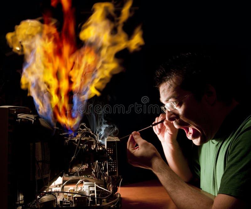 Homme réparant l'ordinateur sur l'incendie photos stock