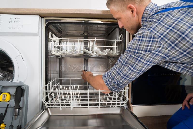 Homme réparant le lave-vaisselle photo stock