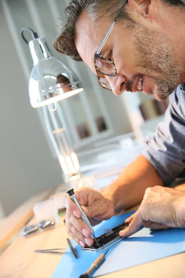 Homme réparant le smartphone cassé images libres de droits