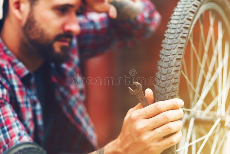 Homme réparant le vélo photo stock