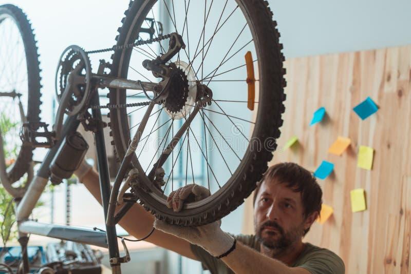 Homme réparant le vieux vélo de montagne dans l'atelier images stock