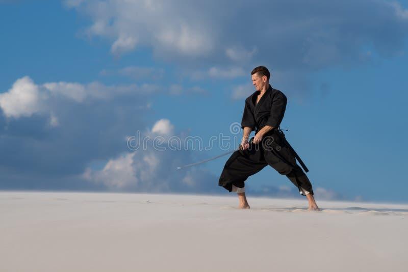 Homme résolu pratiquant des arts martiaux japonais dans le désert image stock