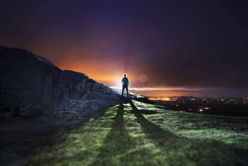 Homme rétro-éclairé sur le sommet de montagne au-dessus de la ville photographie stock