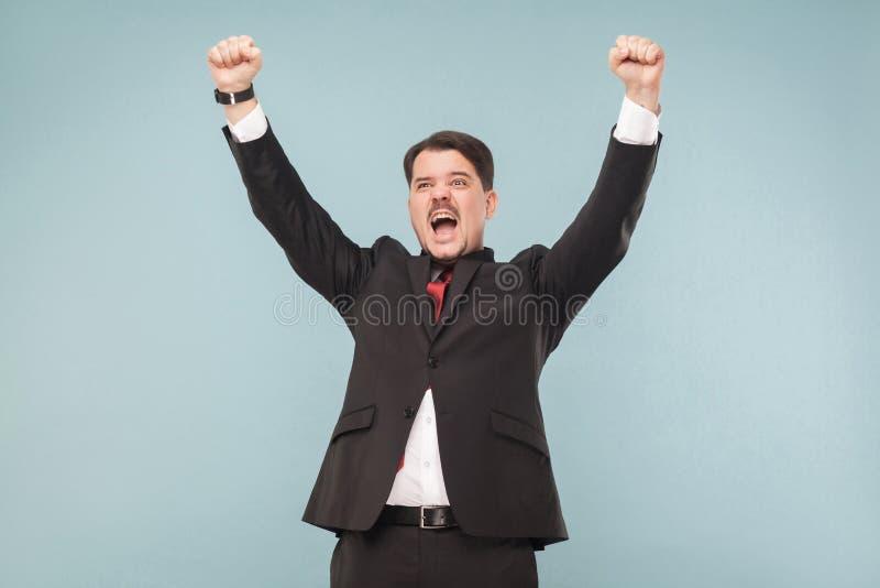 Homme réussi de bonheur dans la victoire de costume photo stock